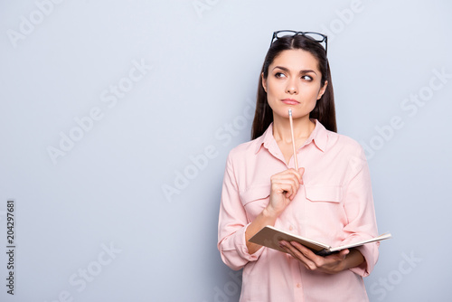 Fototapeta Portrait with copyspace of thoughtful concentrated busy charming woman having notepad and pen in hands planning, expertising, analyzing isolated on grey background, advertisement concept obraz