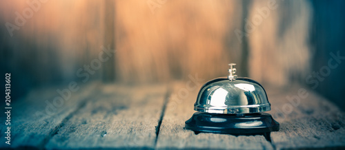 Fotografering Bell metal service on wood ground with blurred wooden background