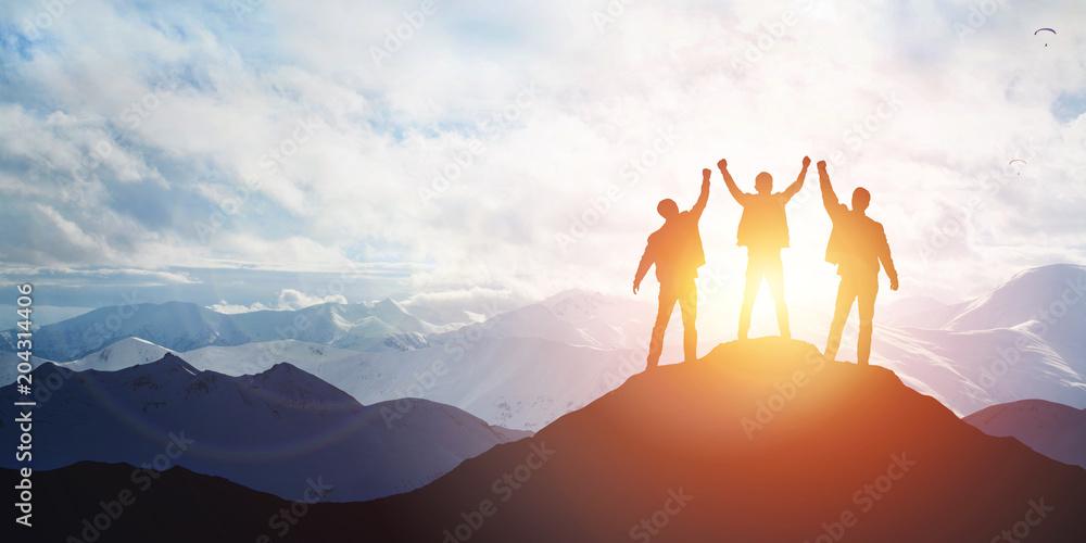 Fototapeta Silhouette of the team on the peak of mountain