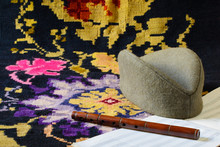 Sajkaca, A Serbian Folk Hat, A Hand-carved Frula (a Shepherd's Pipe), And A Partially Visible Blank Six-stave Music Paper Are Lying On A Kilim, A Traditional Handmade Flat-woven Floor Rug.