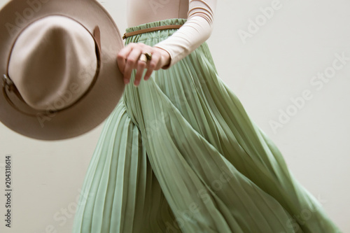 Fotografie, Obraz Hat, beige blouse and turqoise pleats skirt on light street backgraund