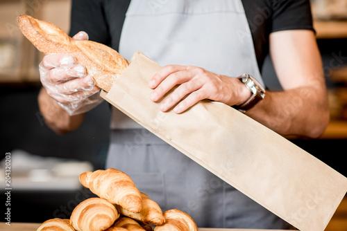 Spoed Fotobehang Bakkerij Packing bread into the paper bag