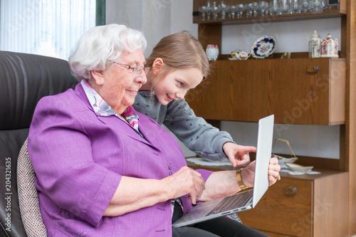 Fotografía  Großmutter zeigt ihrem Enkelkind etwas lustiges auf ihrem Laptop
