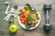 Healthy food , apple, dumbells , sport suit and measuring tape with fork and spoon on the wooden table ,Fitness and health concept.