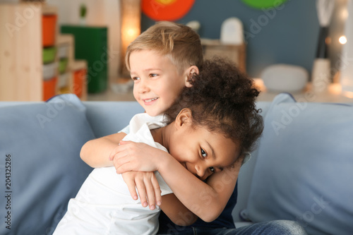 Photo Cute boy and African-American girl indoors. Child adoption