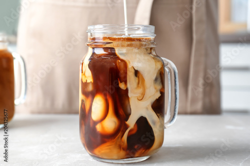 Pouring milk into mason jar with cold brew coffee on table Canvas Print