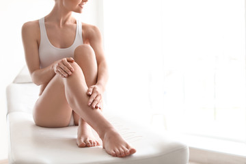 Young woman showing smooth silky skin after epilation at home