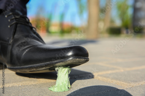 Fotografie, Obraz  Man stepping in chewing gum on sidewalk. Concept of stickiness