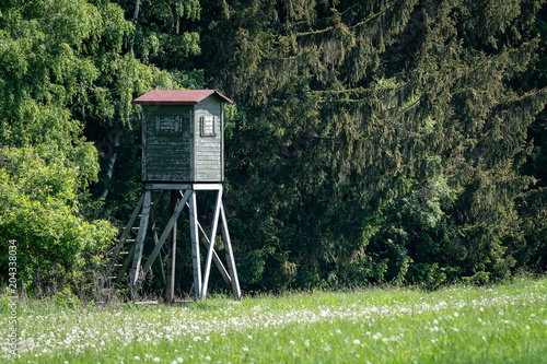 Foto op Canvas Jacht Wooden lookout tower for hunting in the woods and on meadow