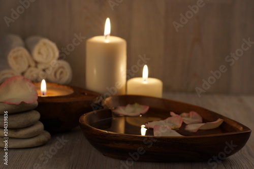 Burning white candles and spa treatment set, water with rose petals and towels Canvas Print