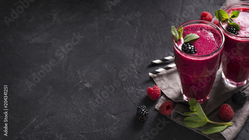 Blackberry and raspberry smoothies in glass with mint leaf and raw beeries
