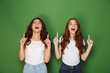 Leinwandbild Motiv Portrait of two pretty women with red hair in white t-shirts smiling and pointing fingers upward in excitement, isolated over green background