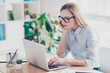 Portrait of smart agent, charming teacher, pretty woman, nice assistant in glasses working online on pc, using internet, looking at screen of laptop, sitting at desktop in work place, station