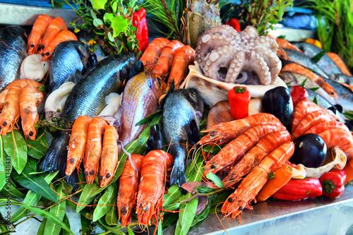 Foto auf Gartenposter Schalentier Sale of fresh frozen arranged fish on ice in farmer's bazaar. Open showcases of seafood market.