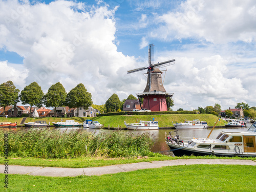 Fotografiet  Canal and windmill on fortifications of fortified town of Dokkum, Friesland, Net