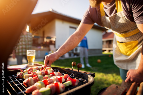 Poster Biere, Cidre Dedicated man turning vegetables and meat on a stick to grill on other side as well while rest of the family is scattered around the house yard.