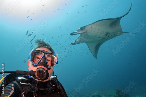 Poster Duiken scuba diver and Manta in the blue ocean background portrait