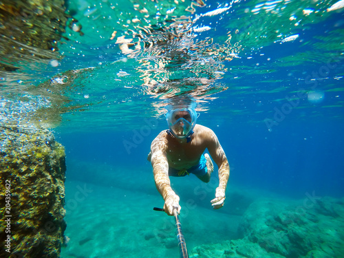 Wall Murals UFO Underwater view of a young diver man swimming in the turquoise sea under the surface with snorkeling mask for summer vacation while taking a selfie with a stick.
