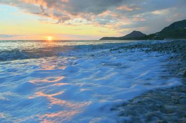 Seascape with sea foam at sunset.