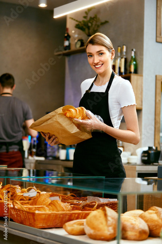 Tuinposter Bakkerij Bakery Shop. Happy Woman Selling Pastry