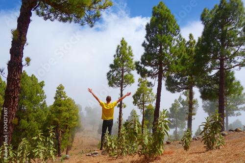 Tuinposter Canarische Eilanden Young man on the top of a volcano which is a part of a hiking trail GR131 Ruta de los Volcanes leading from Fuencaliente to Tazacorte on La Palma, Canary Islands, Spain