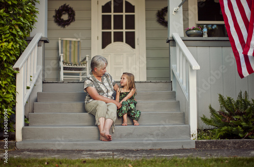 Happy senior woman sitting on front steps with her young granddaughter.