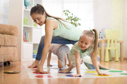 Valokuva Young mom playing twister game with her children daughters