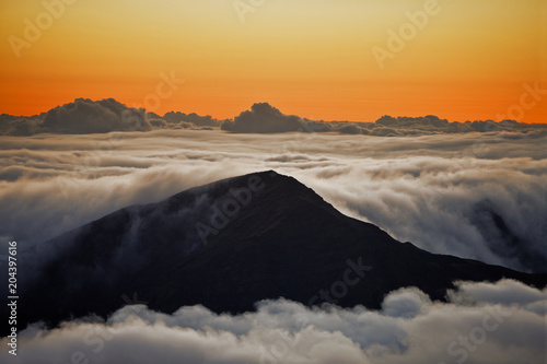 Tuinposter Hemel Silhouette of mountains surrounded by a sea of clouds at sunset.