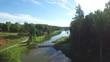Пейзаж реки возле леса. / Вид с высоты птичьего полета на реку, мост через реку. По реке плывут белые лебеди.