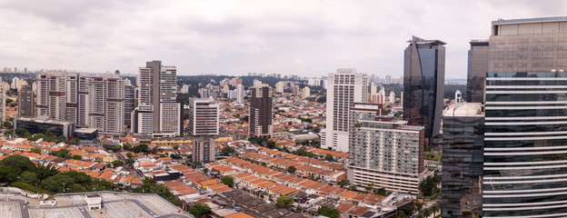 Fototapeta Aerial view of Sao Paulo with business buildings and houses on cloudy winter day.