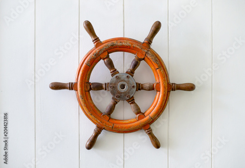 Fotografía  Old boat steering wheel mounted on the white wall