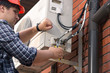 Closeup image of male repairman connecting air conditioner pipes and tubes