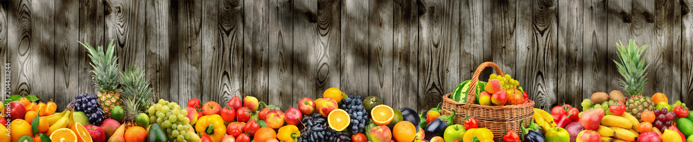 Panoramic photo healthy vegetables and fruits on background dark wooden wall.