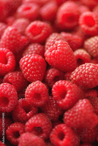 Deurstickers Textures Ripe raspberries macro. Selective focus. Fruit background with copy space. Sunny summer and berries harvest concept. Sunlight effect. Vegan, vegetarian, raw food.