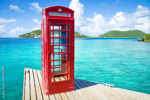 Obraz na plátně  Classic red English telephone booth on a dock in the British Virgin Islands surround by beautiful turquoise Caribbean sea