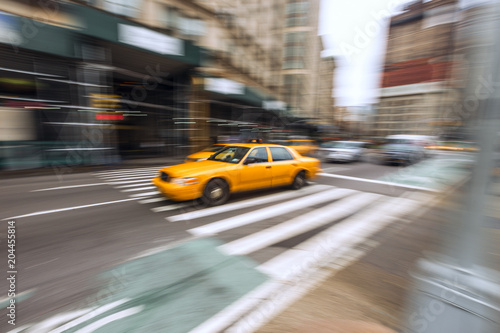 Foto op Plexiglas New York TAXI A traditional NYC taxicab drives down a Manhattan street with motion blur captured with slow shutter speed directly in image