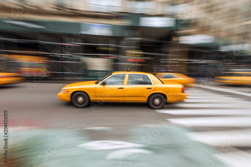 Deurstickers New York TAXI A traditional NYC taxicab drives down a Manhattan street with motion blur captured with slow shutter speed directly in image