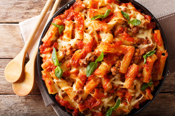 Casserole ziti pasta with minced meat, tomatoes, herbs and cheese close-up. Horizontal top view