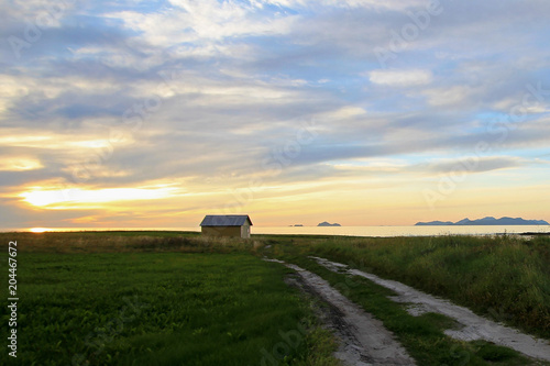 Poster Kust Beautiful yellow house at the coast of Lofoten Islands with view to the Vesteralen Islands at sunset, Norway, Scandinavia, Europe