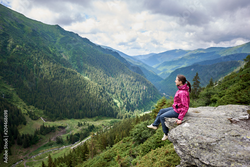 Obraz Smiling beautiful female tourist sitting on rock edge admiring breathtaking view of green grassy slopes and mountains with trees, fir trees and pines in Romania. Woman climber happy amazing nature - fototapety do salonu