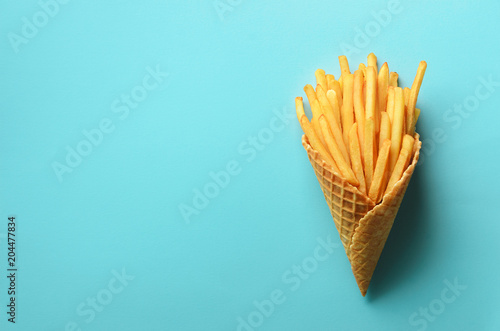 Fried potatoes in waffle cones on blue background Fotobehang