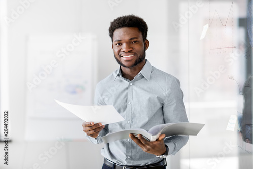 Fotobehang Stof business, people and corporate concept - smiling african american businessman with folder at office