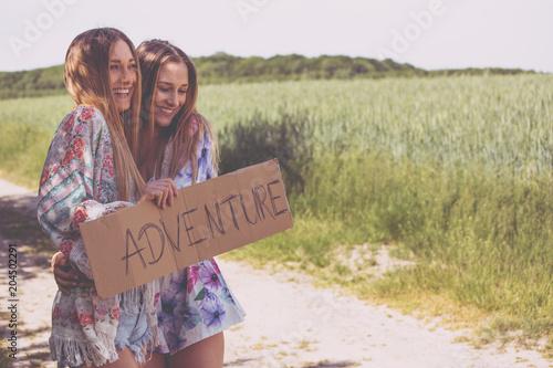 Obraz zwei freundinnen warten auf eine mitfahrgelegenheit. abenteuer urlaub - fototapety do salonu