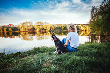 Blonde With Curly Hair And Husky Sit Their Back And Look At The Landscape On The River Bank In The Summer