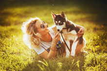 A Small Husky Sits On The Meadow Near The Girl And Looks At The Ice Cream In Her Hands In The Park In The Summer