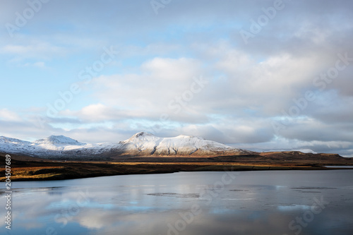 Foto op Canvas Blauwe hemel Mountain road leading to the peaks in Iceland.