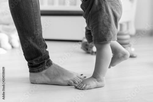 Fotografía  Closeup black and white image of baby's feet next to mother's on wooden floor at