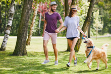 Young Couple Running And Playing With Their Dog While Out On A Walk