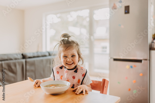 adorable funny toddler girl eating soup at the modern open kitchen