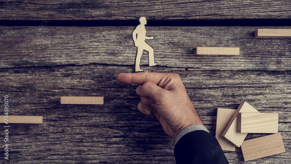 Fototapeta Businessman supporting paper cut out of a man climbing stairs